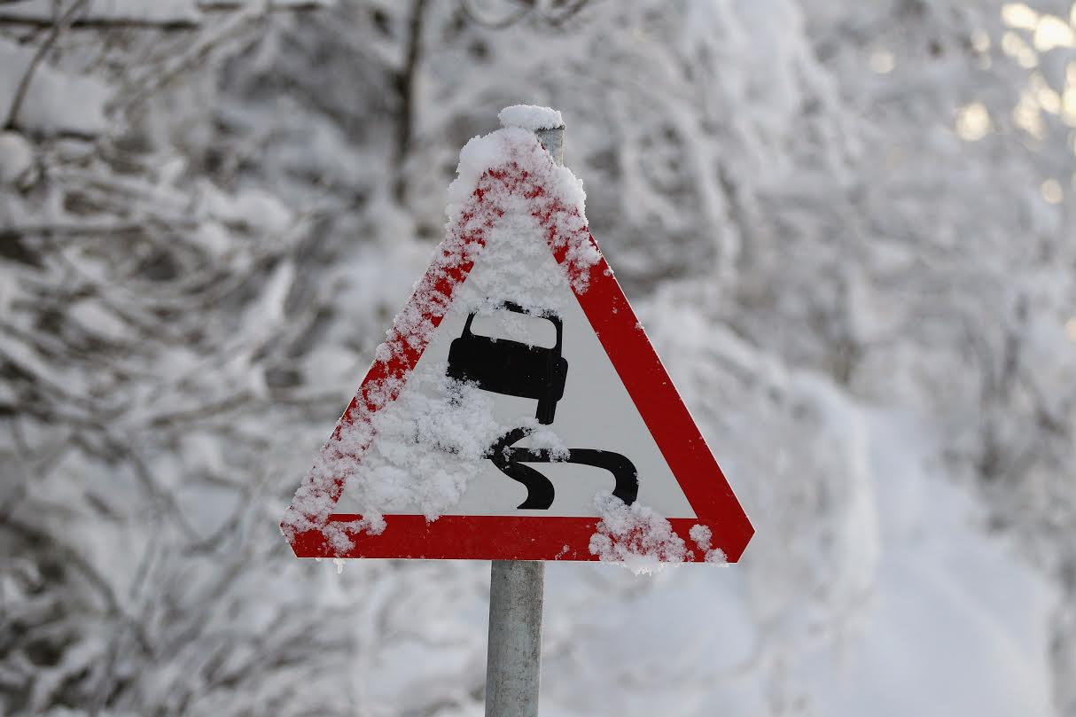 HARTHILL, UNITED KINGDOM - DECEMBER 07: Snow covers part of a road sign warning motorists of the risk of skidding on approach to Harthill service station M8 west bound on December 7, 2010 in Harthill, Scotland. Scotland's main motorway networks were struggling to open following a night of severe weather leaving people stranded in vehicles overnight. (Photo by Jeff J Mitchell/Getty Images)